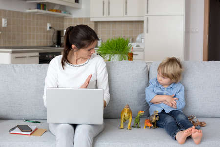 Mother, working on her laptop and taking phone calls, child playing next to her at home while mom having home office Фото со стока