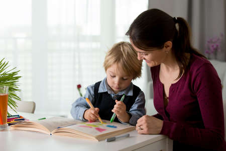 Cute preschool child, blond boy, filling some homework in a work book and coloring, mother helping him at home