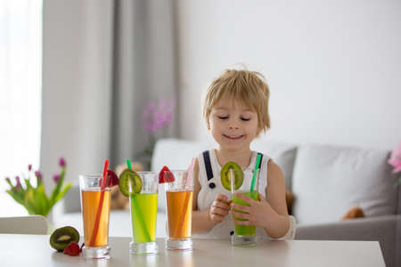 Cute toddler child, blond boy, drinking freshly made fruit juice at home, four glasses full of fresh juice