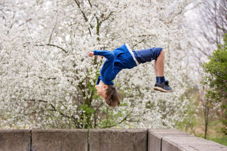 Teen child, boy, making summersaults in the park, springtime