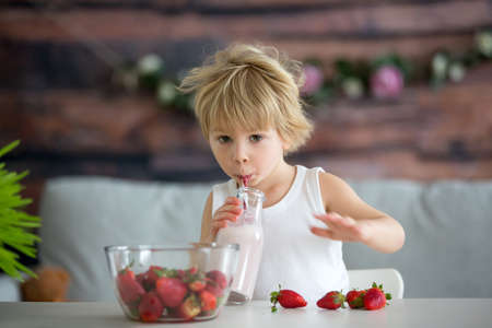 Cute toddler child, blond boy, drinking smoothie and easting strawberries at home