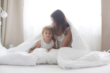 Beautiful blond child and his mother, playing at home in the morning in bed, smiling, laughing and having fun together Фото со стока