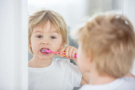 Cute toddler child, blond boy, brushing his teeth at home, isolated Фото со стока