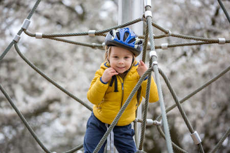 Cute toddler boy, playing on the playground springtime Фото со стока
