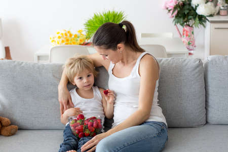 Mother and child, eating strawberries and having fun at home, sitting on the couch