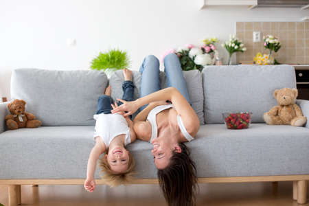 Mother and toddler child, hanging upside down from a couch at home, smiling happily