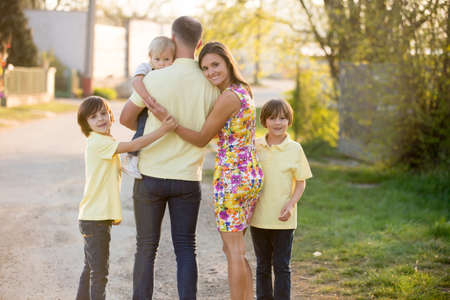 Beautiful family, mother, father and three kids, boys, having familly outdoors portrait taken on a sunny spring evening, beautiful blooming garden, sunset time, back lit. Parents and children have fun