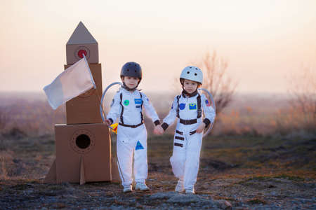 Two adorable children, boy brothers, playing in park on sunset, dressed like astronauts, imagining they are flying on the moon Фото со стока