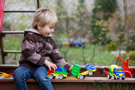 Toddler child, boy, playing in sandpit in backyard in garden