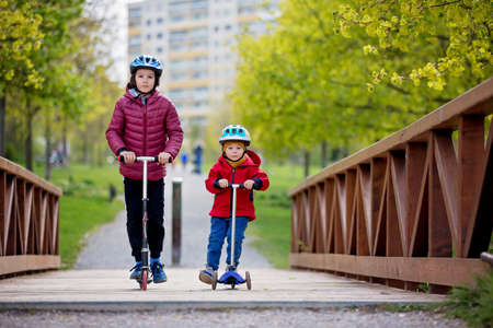 Children, brothers, riding scooters in the park together, spring sunny day Standard-Bild