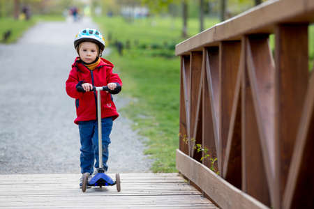 Child, toddler boy, riding scooters in the park, spring sunny day Standard-Bild