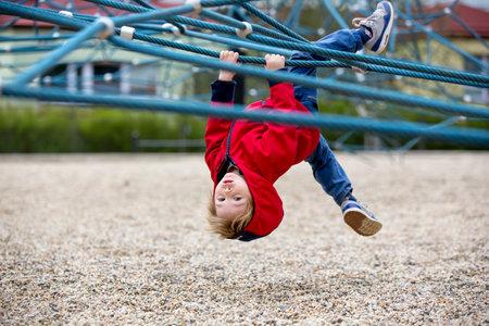 Cute toddler boy, playing on the playground springtime Standard-Bild