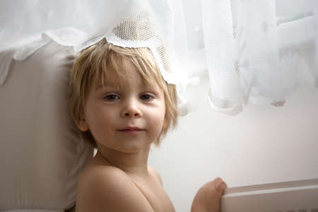 Sweet blond toddler child, boy, hiding behind the curtain at home, smiling happily
