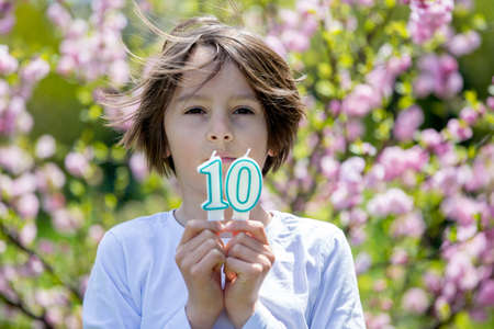 Child, holding number candles with 10 on them, for his birthday