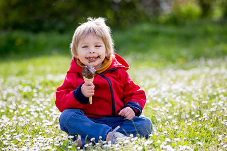 Cute blond child, boy, eating ice cream in the park, springtime
