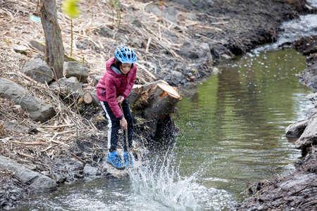 Preteen child, boy, playing at the pond, splashing water