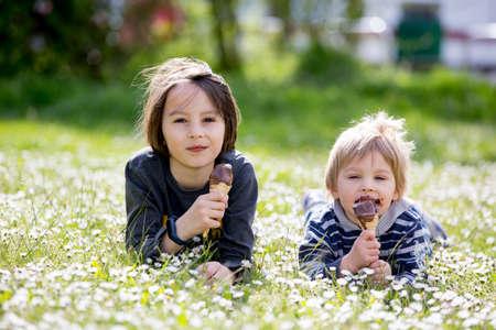 Cute children, boys, eating ice cream in the park, springtime