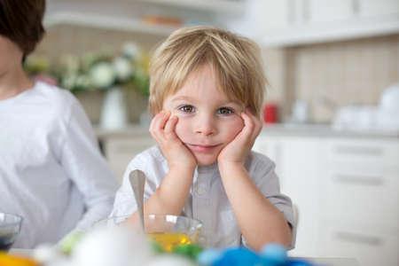 Children, boy siblings, coloring eggs for Easter at home Standard-Bild