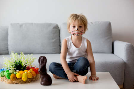 Little toddler boy, child with rabbit painted on the face, eating chocolate bunny at home