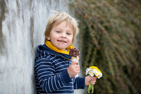 Cute blond child, boy, eating ice cream in the park, holding little bouquet of wild flowers, springtime