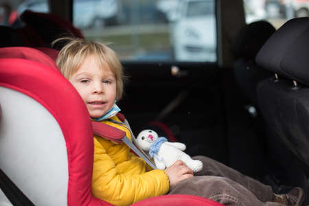 Little blond toddler child, kid, eating, waffle in car seat, sitting buckled Standard-Bild
