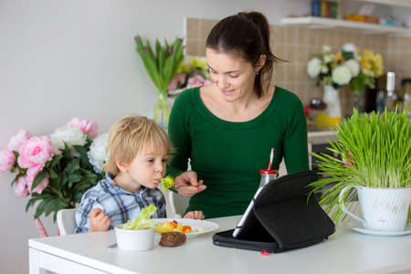 Little toddler child, blond boy, eating boiled vegetables, broccoli, potatoes and carrots with fried chicken meat at home, while watching movie on tablet, mom giving him bites