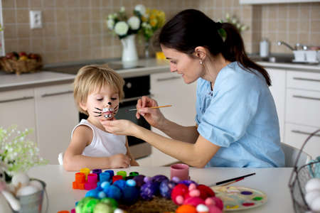 Mother painting on little blond toddler boys' face easter bunny at home Standard-Bild