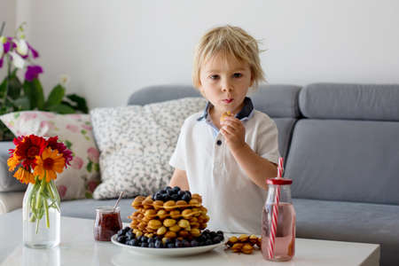 Sweet toddler child, boy, eating bubble waffles with fruits at home for breakfast, flowers on the table Standard-Bild