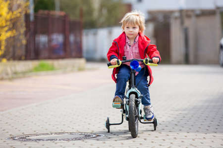 Little child, blond boy, learning how to ride a bicycle in the park using helping wheels on the side, springtime Standard-Bild