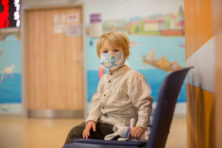 Child, boy, sitting in the waiting room in emergency, waiting for examination and xrays