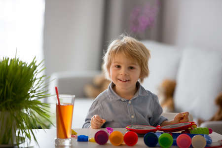Cute blond child, sweet boy, playing with play doh modeline at home, making different objects