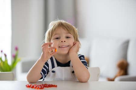 Cute little child, toddler boy, eating alfa omega 3 child supplement vitamin pills at home for better immunity