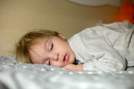 Toddler sleeping at home at night, hugging little toy, soft light Standard-Bild
