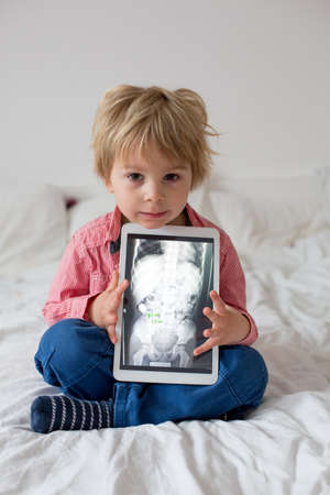 Toddler child, blond boy, holding x-ray picture on tablet of child body with swallowed magnet showing, child swallow dangerous object Standard-Bild