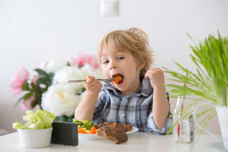 Little toddler child, blond boy, eating boiled vegetables, broccoli, potatoes and carrots with fried chicken meat at home, while watching movie on mobile phone