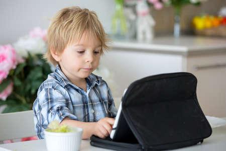 Little toddler child, blond boy, licking lollipop at home while watching movie on tablet Standard-Bild