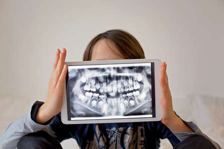Child, preteen boy, holding tablet with a picture of his x-ray teeth from the dentist
