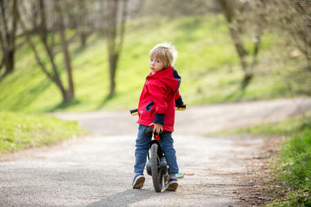 Little boy, learning how to ride a bike in the park, springtime Standard-Bild