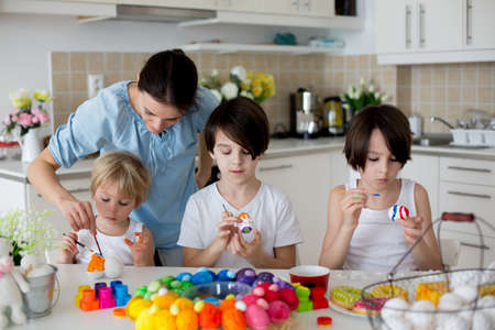 Three children, sibling brothers, painting easter eggs for decoration at home, mother helping them Standard-Bild