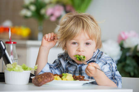Little toddler child, blond boy, eating boiled vegetables, broccoli, potatoes and carrots with fried chicken meat at home, while watching movie on tablet