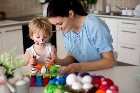 Beautiful blond child, toddler boy, painting easter eggs with mother at home, making easter wreath with rainbow colors Standard-Bild