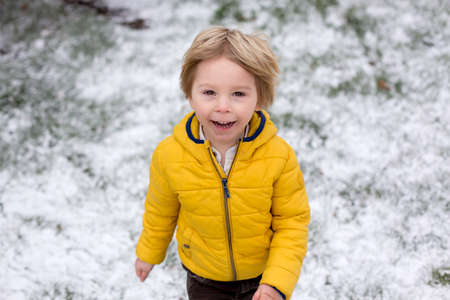 Cute blond toddler child, boy, running around blooming yellow bush, spring time, while snowing, unusual spring weather with snow Standard-Bild