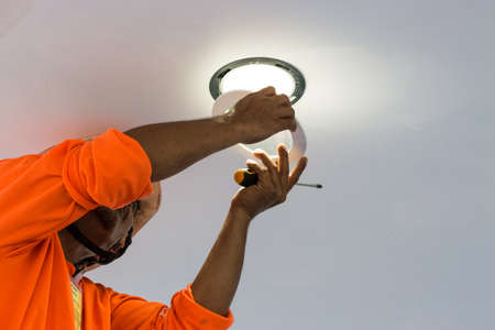 electrician worker in uniform installing or replacing spot light lamp into ceiling