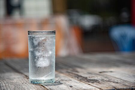 Glass of water placed on a wooden table, selective focus, blur some part.