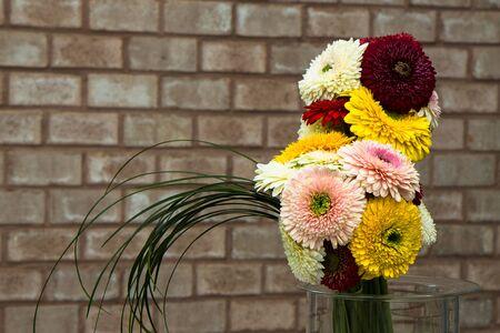 beautiful gerbera bouquet towards a brick wall
