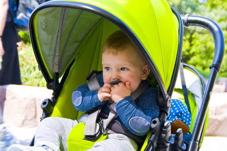 Little boy is sitting in pram with a smiling face and is happy