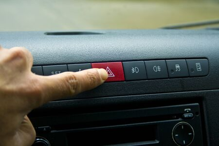 Finger hitting car emergency red light button