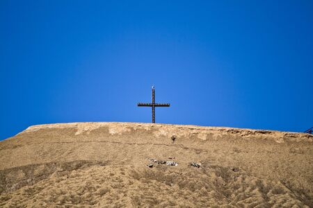 A Christian cross on an artificial mountain where mining is operated in Hesse, Germany