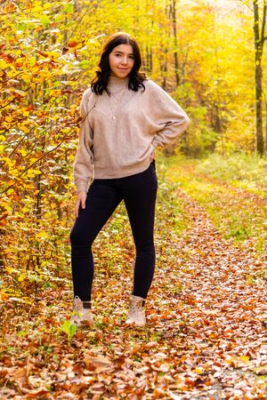Young girl with beige sweater and black jeans stands in the colorful autumn forest in October