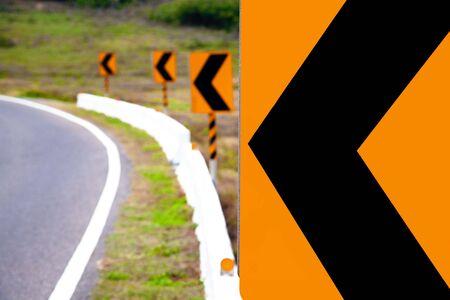 交通: 左の道路の警告標識を回す 写真素材